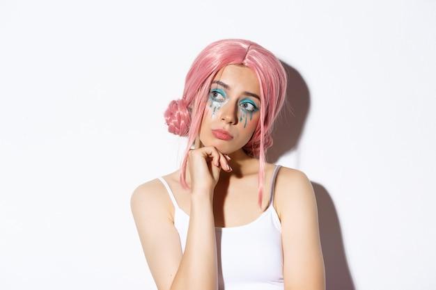 ピンクのかつらで懐かしい悲しい少女のクローズアップ、白い背景の上に立って、思慮深く左を見て