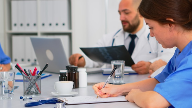 방사선과 의사 동료들이 백그라운드에서 엑스레이를 분석하고 노트북에 글을 쓰는 동안 클립보드에 메모를 하는 간호사를 닫습니다. 의료 회의, 브레인스토밍을 하는 전문 팀 작업자