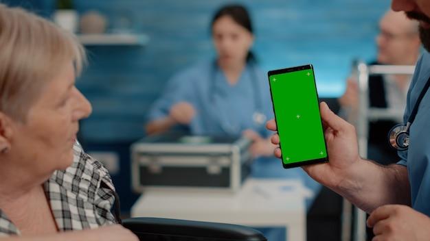 緑の画面で電話を垂直に表示している看護師のクローズアップ