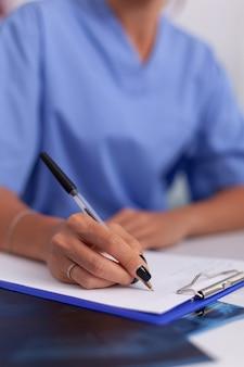 병원 사무실에서 클립보드에 환자 진단을 쓰는 간호사의 닫습니다. 모니터, 약, 직업, 스크럽을 보고 있는 현대 클리닉에서 컴퓨터를 사용하는 의료 의사.