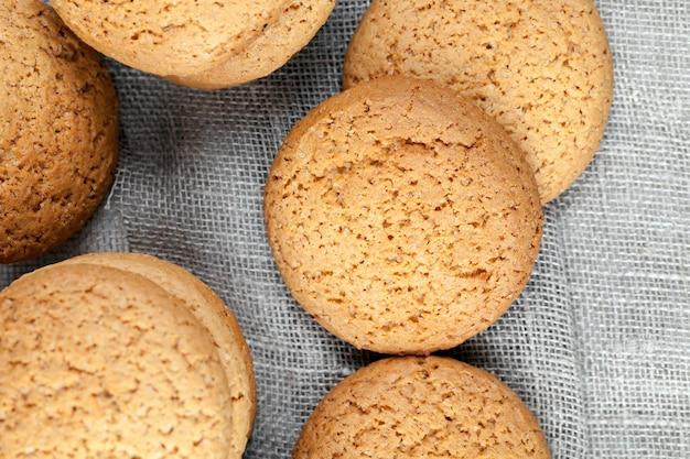 カロリーがあまり高くないオートミールクッキー、あまり甘くないドライでカリカリのクッキー、オートミールで焼いた多孔質クッキーのクローズアップ