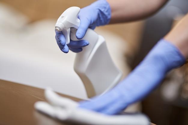 Горничная в перчатках распыляет дезинфицирующее средство на мебель во время уборки в гостиничном номере. концепция домашнего хозяйства и гигиены