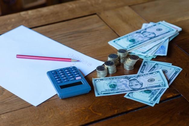 Закройте офисный стол с калькулятором, документами и деньгами