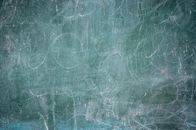 白いチョークの背景、グランジテクスチャと古い黒板のクローズアップ。
