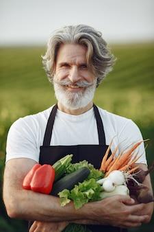야채 바구니를 들고 오래 된 농부 닫습니다. 남자가 정원에 서 있습니다. 검은 앞치마에 수석.