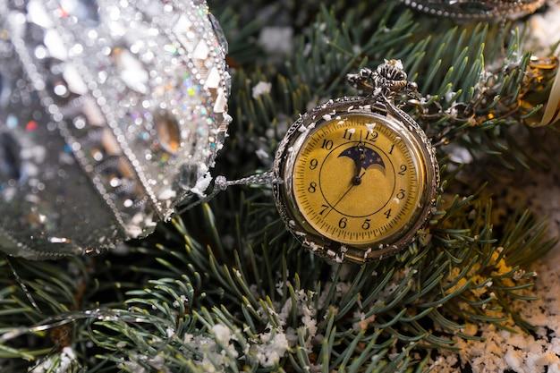 きらめく銀のクリスマスボールで飾られた常緑樹の雪に覆われた小枝にぶら下がっている昔ながらの懐中時計のクローズアップ