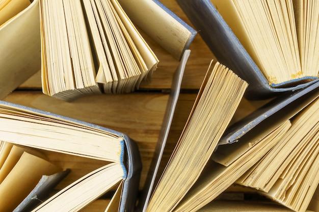 木の表面の古いハードカバーの本のクローズアップ。本の上面からの表面。開いた本、めくったページ。