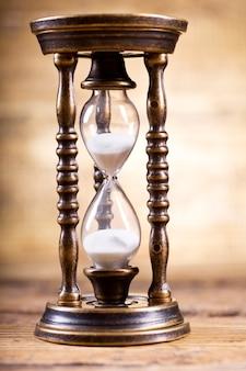 나무 배경에 오래 된 모래 시계를 닫습니다