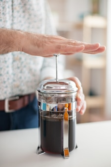 Закройте старика, делая кофе с французской прессой. пожилой человек утром наслаждается свежим коричневым кофе в кофейной чашке эспрессо из винтажной кружки, фильтрует расслабляющий освежающий напиток