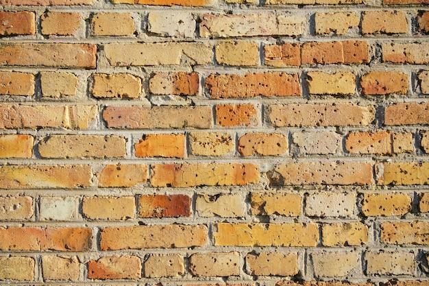 背景とテクスチャの使用のための古いオレンジ色のレンガの壁のクローズアップ