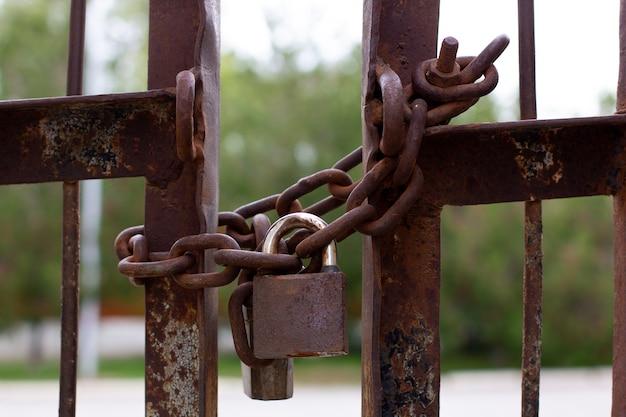 철 울타리에 오래 된 녹슨 자물쇠 체인 닫습니다.