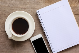 Close up of old wooden desktop with notebook, smartphone and coffee cup.