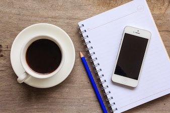 Close up of old wooden desktop with notebook, smartphone, coffee cup and pencil.