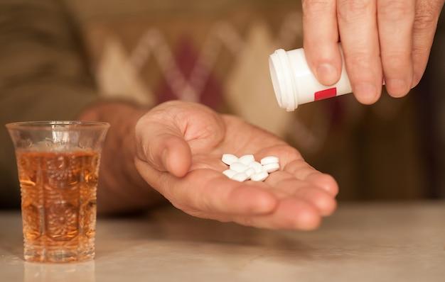 Крупный план пожилого человека, потягивающего наркотики с алкоголем