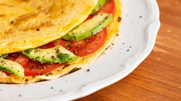 접시에 토마토와 아보카도와 오믈렛의 클로즈업