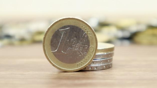 Крупный план монеты в один евро на рабочем столе. европейские металлические наличные деньги и на заднем плане монеты центов евро не в фокусе.