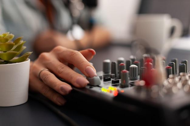 新しいクリエイターのホームスタジオにあるミキサー付きのオンラインライブポッドキャストスタジオデスクのクローズアップ。加入者向けのプロ仕様の機器を使用してソーシャルメディアコンテンツを記録するインフルエンサー