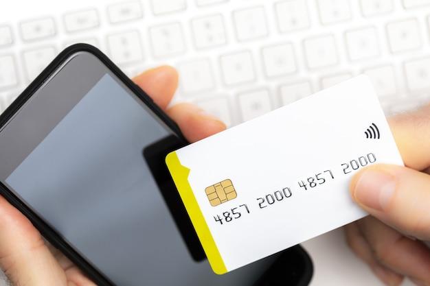 コピースペースのあるコンピューターのキーボードでスマートフォンとクレジットカードで支払うオンライン買い物客のクローズアップ。オンラインショッピング。