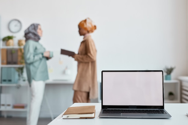Закройте открытый ноутбук с пустым белым экраном с двумя этническими женщинами, работающими в фоновом режиме, копией пространства