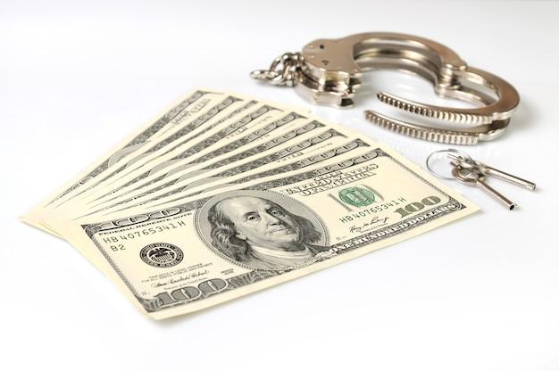 オープンメタルの手錠、鍵、白い背景の上に分離された米ドルの現金のスタックのクローズアップ。違法な金儲け、賄賂、汚職シリーズ