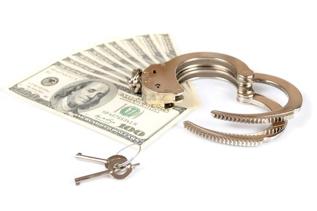 Крупный план открытых металлических наручников, ключей и стопки наличных американских долларов, изолированных на белом фоне
