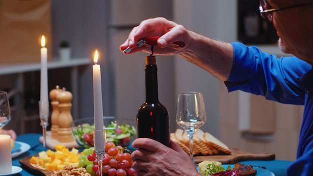 낭만적인 저녁 식사 중에 와인 한 병을 여는 것을 닫습니다. 나이 든 노부부는 부엌 테이블에 앉아 이야기하고 식사를 즐기고 식당에서 기념일을 축하합니다.