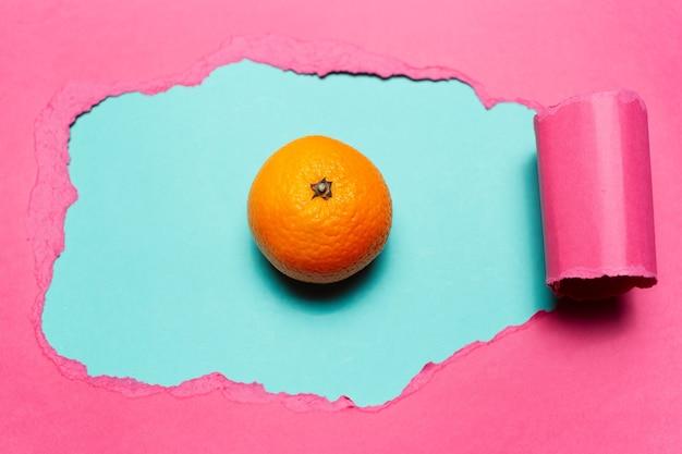 Крупный план оранжевых фруктов на голубом фоне в отверстии из рваной бумаги розового цвета.