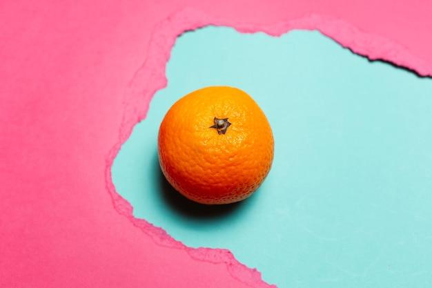 ピンク色の破れた紙の穴のシアンの背景にオレンジ色の果物のクローズアップ。