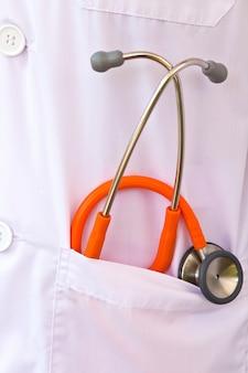 ポケットの中のオレンジ色の聴診器のクローズアップ