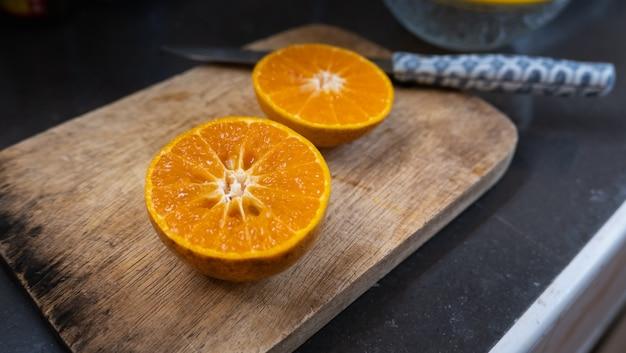 Крупным планом апельсинов, чтобы приготовить апельсиновый сок на столе