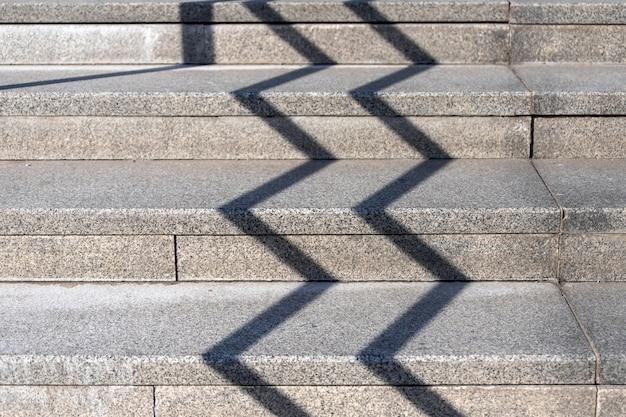 기하학적 그림자가 있는 콘크리트와 시멘트로 만들어진 일반 석재 단순 계단의 클로즈업