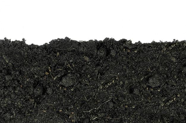 白い背景(土壌、地球、地面)の有機質土壌のクローズアップ