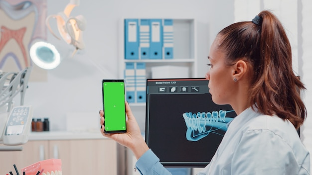 緑の画面でスマートフォンを保持している歯科矯正医のクローズアップ