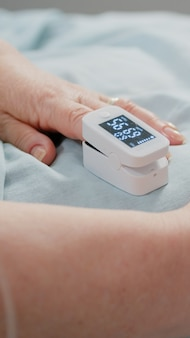 低酸素飽和度を示す指の酸素計のクローズアップ