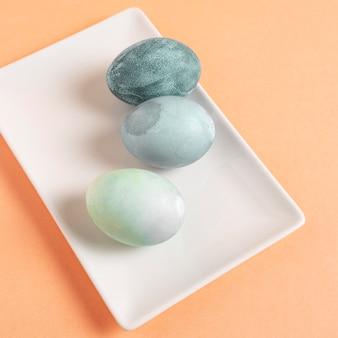 Крупный план расписных пасхальных яиц на тарелке