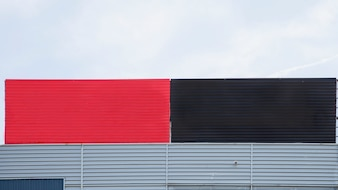 Close-up of painted red and black big blank hoarding against sky