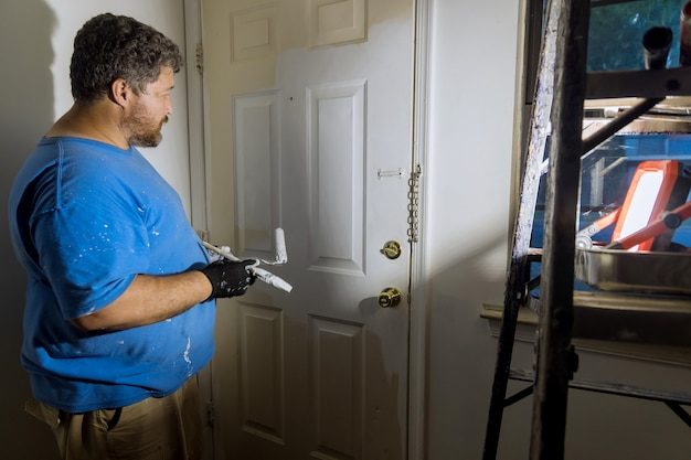 Крупный план рук художника в перчатках, красящих дверную раму с помощью ручного валика на реставрации рабочего дома