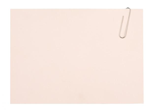 空白の紙シートの背景を保持しているペーパークリップのクローズアップ