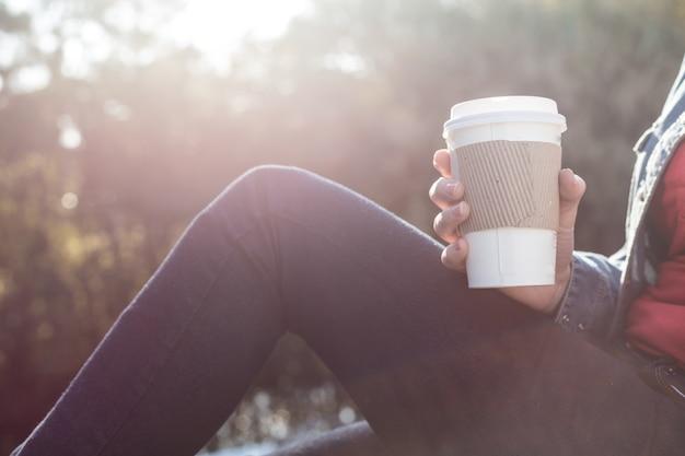 Крупным планом бумажный стаканчик в руке девушки