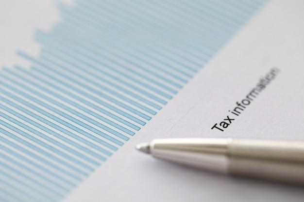 Конец-вверх бумаги с налоговой информацией и серебряной ручкой. макро съемка анализа и диаграмм. черные чернила надпись на документе. концепция бизнеса и расчетов