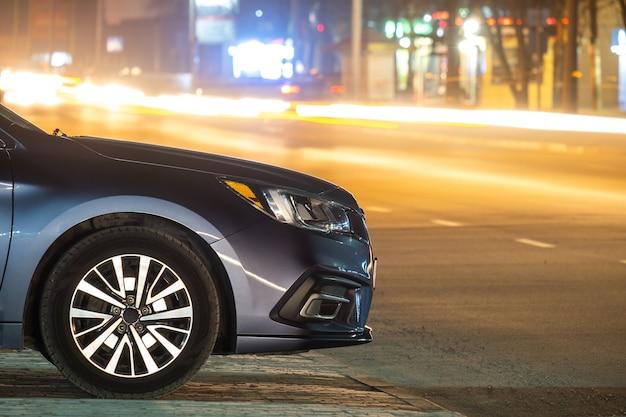 Закройте припаркованный автомобиль на обочине дороги ночью с размытым видом на светофор движущихся транспортных средств на городской улице.