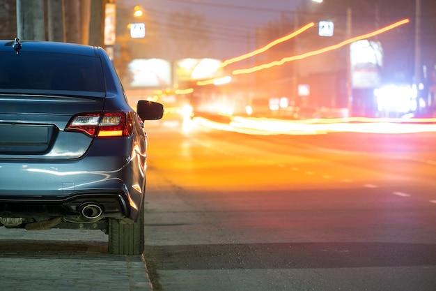 Крупным планом припаркованный автомобиль на обочине дороги ночью с размытым видом на светофор