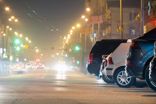Закройте припаркованных автомобилей на обочине дороги ночью с размытым видом на светофор движущихся транспортных средств на городской улице.