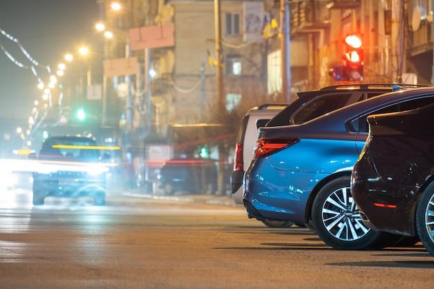 Крупным планом припаркованных автомобилей на обочине дороги ночью с размытым видом на светофор