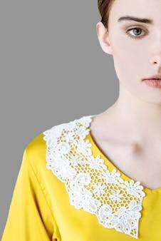 部分のクローズアップ灰色の孤立した背景に黄色いブラウスの女性の顔の一部のクローズアップ灰色の孤立した背景に黄色いブラウスの女性の顔のクローズアップ