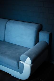 黒レンガの壁の背景に青いソファの一部のクローズアップ。