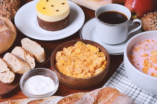 情熱フルーツケーキ、トースト、コーヒー、ヨーグルト、シリアルを閉じます。