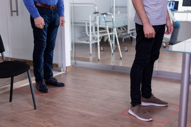 코로나 바이러스에 대한 사회적 거리두기를 존중하는 바닥 표지판의 대기실에 서있는 환자의 닫습니다