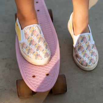 Крупный план узорчатой обуви и розового скейтборда
