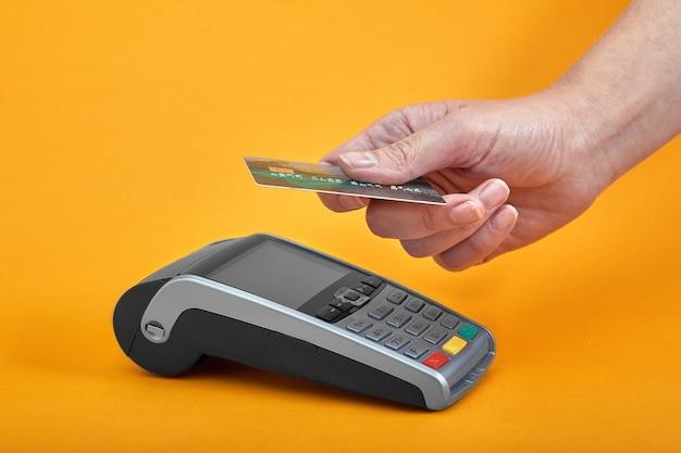 노란색 배경 근처에 플라스틱 카드를 들고 있는 인간의 손으로 결제 기계 버튼의 클로즈업.